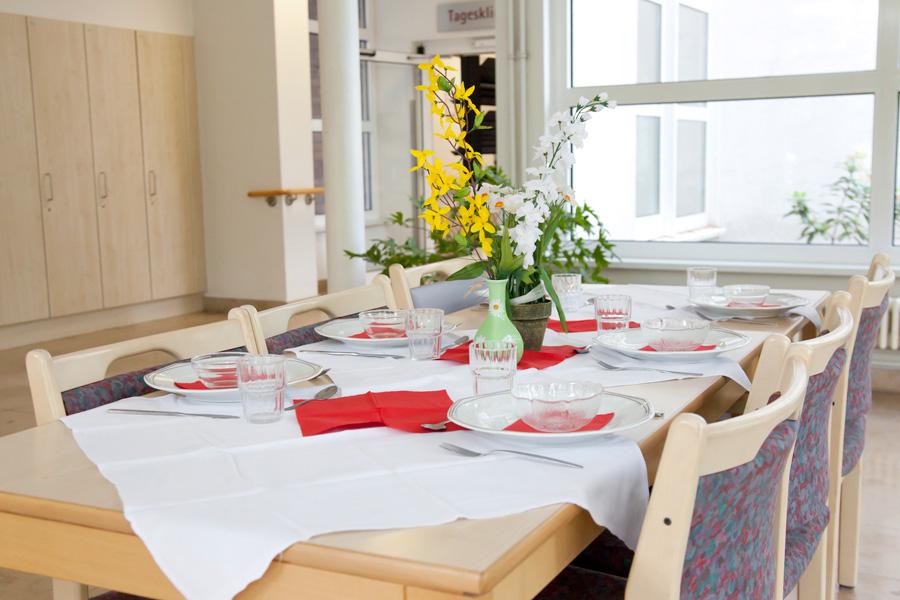 Wintergarten in der Tagesklinik mit gedecktem Tisch für die Teilnehmer am Kochtraining.